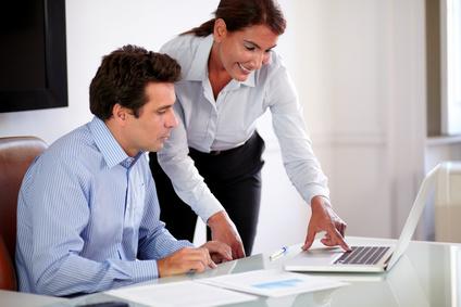 Frau zeigt Mann am Notebook eine neue Aufgabe