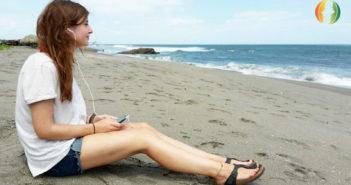 Frau am Strand die mit Jicki Sprachdusche lernt